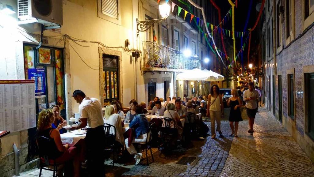 Lissabon Tipps: Abendliche Gasse im Bairro Alto, Leute im Restaurant