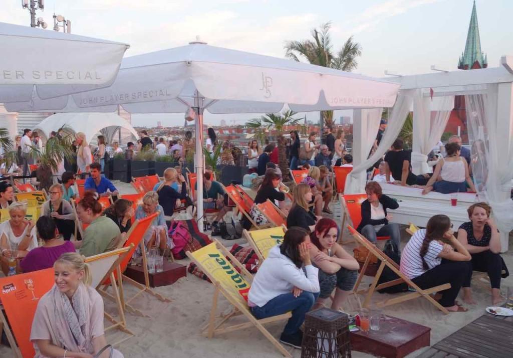 Berlin Hotspots - Rooftop-Bar Deck 5, Leute im Sand auf Liegestühlen...