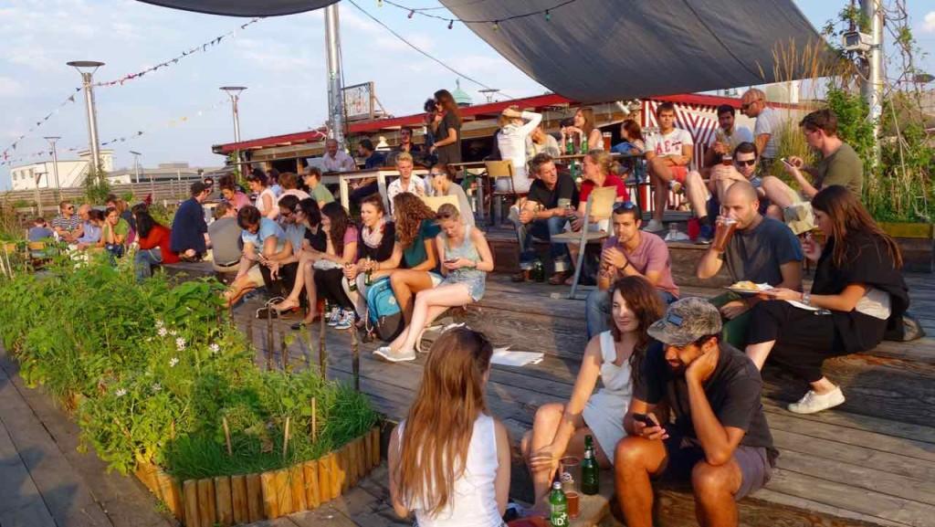 Berlin Hotspot, Rooftop-Bar Klunkerkranich, Warten auf den Sonnenuntergang. Gäste auf Stufen