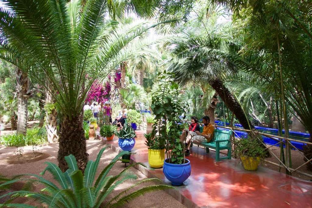 Jardin Majorelle Marrakesch, Garten mit Palme, Vasen, Leuten auf Bank