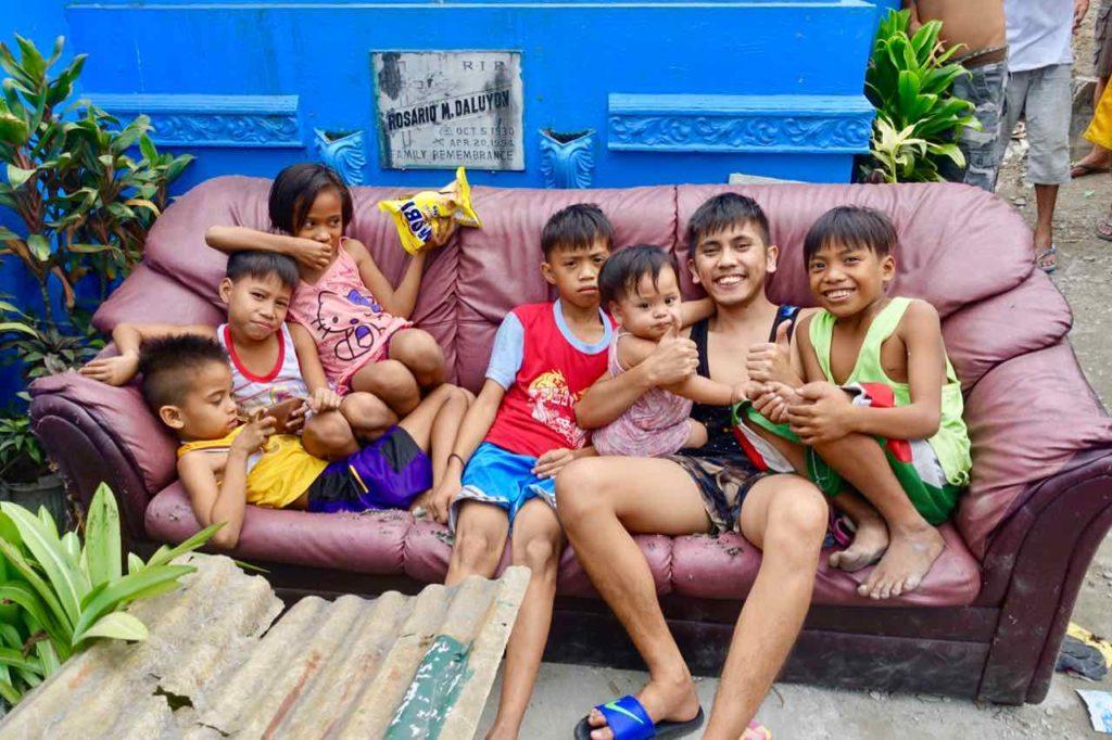Nordfriedhof von Manila: Kinder posieren auf Couch für das Foto