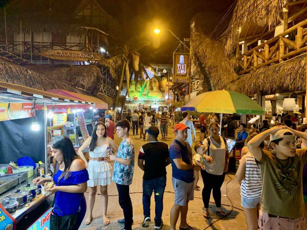 Straße mit Touristen in Montañita am Abend