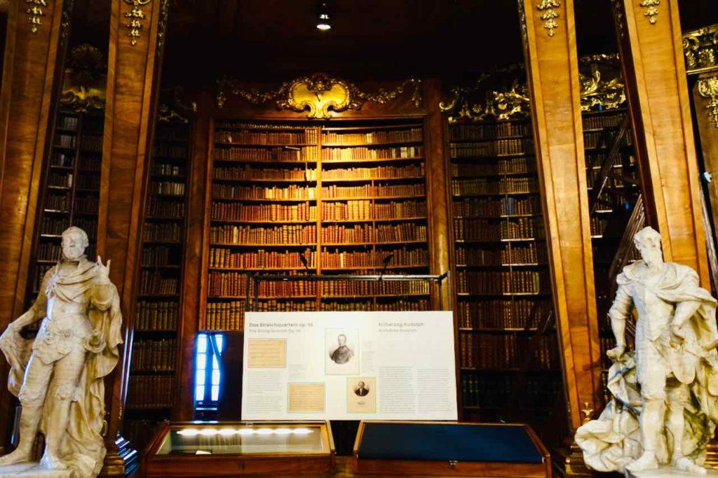 Bücherregal mit Statuen und Schaukästen im Prunksaal der Österreichischen Nationalbibliothek